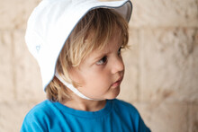 Blond Three Years Old Child Looking Curious To One Side With A White Summer Hat Dressed In A Blue T-shirt