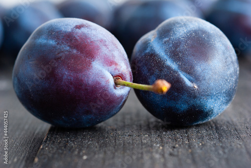Fotografie, Obraz plums on black wood table, front view