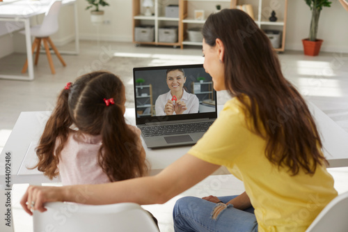 Slika na platnu Back view happy school child together with mom sitting at desk table, looking at
