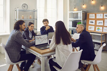Company Workers Sitting Around An Office Table In A Corporate Work Meeting. Business Team Having A Discussion, Considering Ways To Increase Sales And Planning To Enter A New Market With A New Product