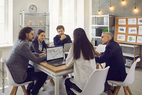 Photo Company workers sitting around an office table in a corporate work meeting