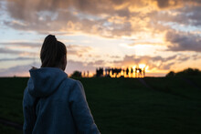 Woman Looking At A Crowd Of People On A Beautiful Sunset Hill