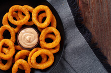 Delicious Homemade Crunchy Fried Onion Rings With Spicy Sauce. Top View. Copy Space