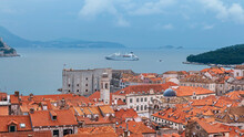 Top View Of Red Tiled Roofs And Bay With Tourist Liner In Ancient Croatian City - Dubrovnik