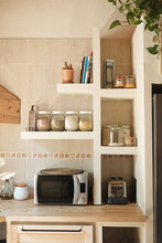 Modern Kitchen With Microwave Oven, Toaster And Jars With Legumes