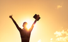 Silhouette Of Inspire Female Holding Up Book To The Sky With Thumbs Up. Education, And Religious Belief Concept
