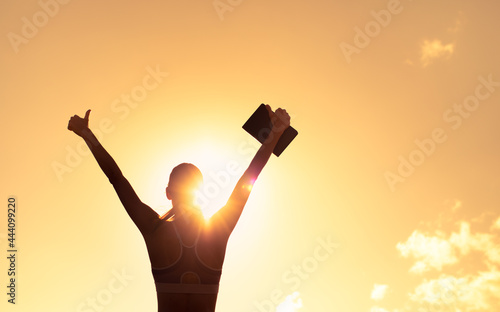 Obraz na plátně silhouette of inspire female holding up book to the sky with thumbs up
