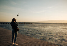 Young Woman Watching People Kitesurfing During Sunset On The Sea