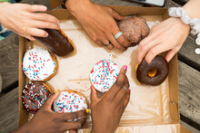 Diverse Hands Grabing Donuts From A Box