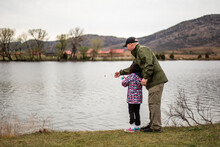 Dad And Daughter Standing On Shore Fishing