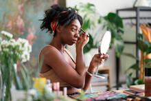 Black Woman Applying Eyebrow Pencil And Doing Makeup
