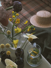 Yellow Summer Flowers In Unusual Vases On The Table