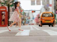 Little Girl Walk On Zebra Crossing In City Street