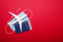 Syringe, Toy Plane, Medical Mask And Passport With Covid-19 Test  With Text 'Covid-19 Tested' Inside It On Red Background. Travel Concept During The Covid-19 Pandemic