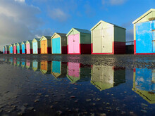Multi Colored Huts On Beach By Buildings Against Sky
