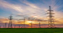High Voltage Lines And Power Pylons In A Green Agricultural Field Against A Saturated Sunset Sky