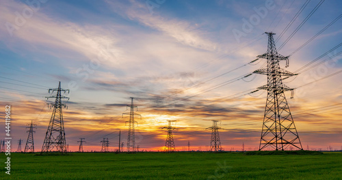 Fotografia high voltage lines and power pylons in a green agricultural field against a satu