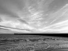 Black And White Cenic View Of Harbour Wall And Sea Against Sky