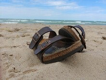 Shoes On Sand At Beach Against Sky