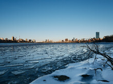 Scenic View Of Ice Covered Charles River With Boston Skyline Against Clear Sky