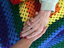 Granddaughter Holding Grandmother's Hand Preceding Final Stage Of Life.