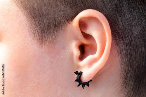 Fotografie, Tablou Black earring in the ear close-up, ear piercing