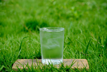 Drinking Water In A Glass With A Glass Of Ice Is Placed On A Wooden Floor On The Bright Green Grass Outdoors.