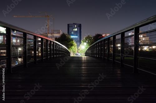Wallpaper Mural Illuminated Footbridge Amidst Buildings In City At Night