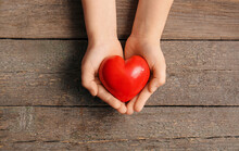 Child's Hands With Red Heart On Wooden Background