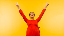 Beautiful Woman In Red Dress Posing Hand Giving The Devil Horns Gesture On Yellow Background