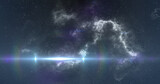White spot of light moving over white nebula in the night sky