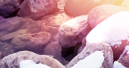 Image of stones in water during winter covered in snow and frost with light spots