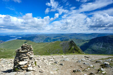 Looking Down Striding Edge Towards Ullswater And Glenridding From The Summit Of Helvellyn In The Lake District. Shot In Landscape With A Stone Cairn In The Foreground