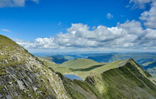 Red Tarn Peeking Over Striding Edge, On Helvellyn In The Lake District Shot On A Summer Day With Blue Skies And White Clouds, With Ullswater In The Far Distance