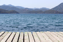 View From Old Wooden Pier To Deep Blue Water And Misty Mountains Covered With Forest. Beach Vacation On The Sea, Background For Summer Vacation And Travel