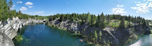 Fotografia, Obraz Panorama with a view of the rocks, grotto and turquoise water of the Marble Canyon in the Ruskeala Mountain Park, where boats float and the sky and trees are reflected on a sunny summer day