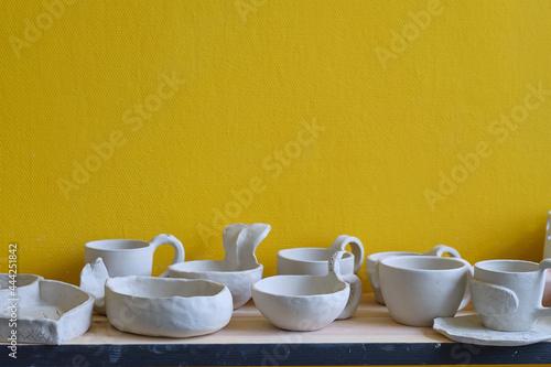 Billede på lærred Unfinished clay pots on shelves as part of a ceramic pottery workshop