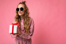 Shot Of Beautiful Positive Young Blonde Curly Woman Isolated Over Pink Background Wall Wearing Pink Sport Clothes And Sunglasses Holding Gift Box And Unboxing Surprise Looking To The Side