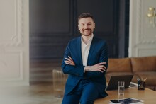 Photo Of Satisfied Bearded Prosperous Businessman Stands Self Assured In Own Cabinet Or Contemporary Office Keeps Arms Folded Dressed Formally Smiles Pleasantly Satisfied With Results Of His Work