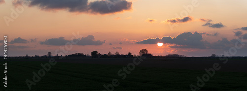 Obraz na plátně Sunset over the agricultural land near Hulst The Netherlands with silhouettes of