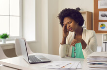 Tired Exhausted Young Dark Skin Woman Experiencing Severe Headache Sitting At Work In Front Of Laptop. Business Woman Needs Rest And Healthy Sleep. Concept Of Fatigue, Exhaustion And Stress At Work.