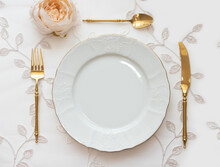 Wedding Table Arranged With Golden Cutlery And White Charger Plate. Mockup For Menu, Invitation Card, Festive Concept In Vintage Style
