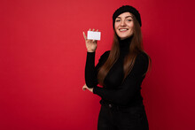 Photo Of Beautiful Positive Young Brunette Woman Wearing Black Sweater And Hat Isolated On Red Background Holding Credit Card Looking At Camera