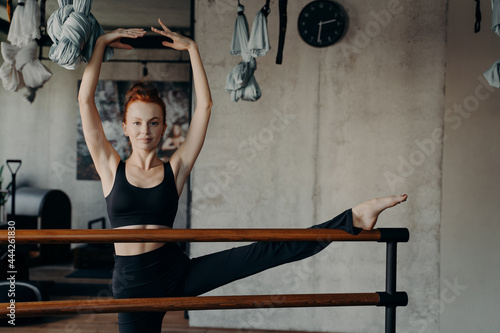 Canvastavla Beautiful slim redhaired woman standing with leg on ballet barre