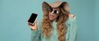 Panoramic photo of beautiful happy young blonde woman wearing sunglasses and summer hat isolated on blue background with copy space holding smartphone showing phone in hand with empty screen display
