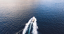 Aerial View Of Boat Crossing Tranquil Blue Sea Water Surface During Winter Season, Top View Of Fishing Vessel In Ocean Water