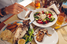 Man Eats Fish With Vegetables And Greek Salad In Outdoors Restaurant. Fresh Seafood Dinner.