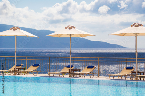 Luxury swimming pool with empty deck chairs and umbrellas at the resort with bea Fototapet