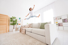 Photo Of Charming Shiny School Girl Wear White T-shirt Smiling Jumping High Sofa Indoors House Home Room