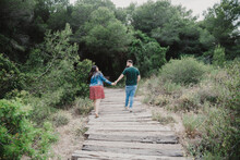 Loving Couple Holding Hands And Walking On Boardwalk In Park